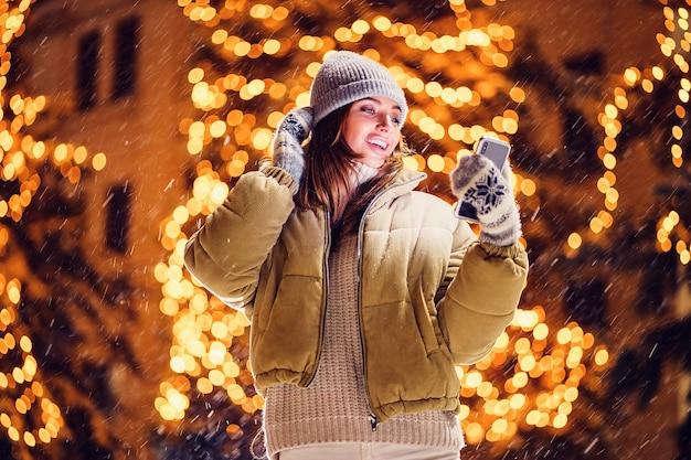 Uma mulher jovem e bonita fazendo selfie ou usando o telefone ao ar livre