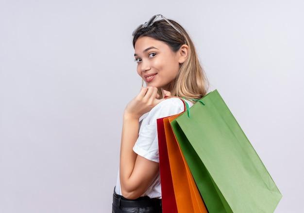 Uma mulher jovem e bonita feliz em uma camiseta branca usando óculos escuros na cabeça segurando sacolas de compras enquanto olha para uma parede branca