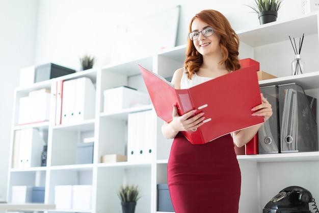 Uma mulher jovem e bonita fica perto de uma pilha no escritório e segura uma pasta com documentos nas mãos dela.