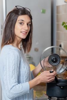 Uma mulher jovem e bonita morena cozinhando na cozinha