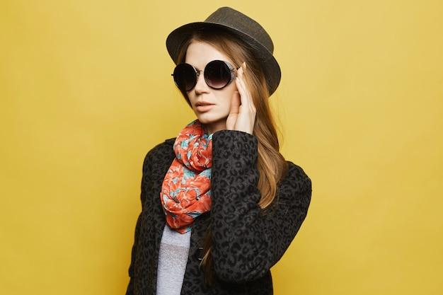 Uma mulher jovem e bonita no casaco elegante, chapéu da moda e óculos de sol posando garota modelo com cabelo loiro em roupa de outono na moda. conceito de moda de rua