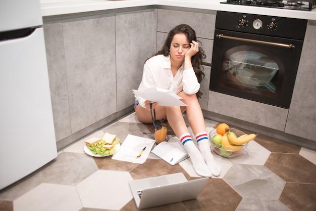 Uma mulher jovem e bonita trabalha a noite toda na cozinha de sua casa, está muito cansada. mas ainda há muito trabalho. trabalhar em casa é difícil e cansativo