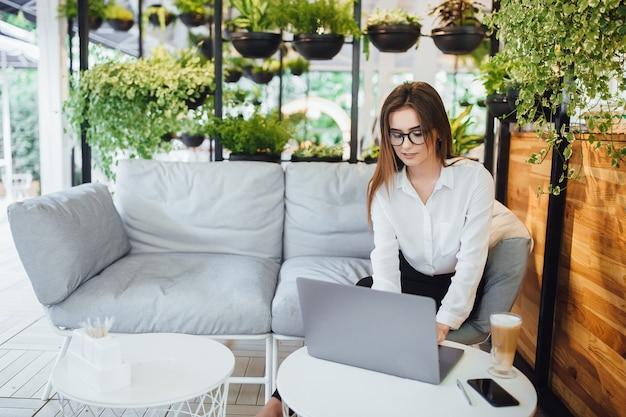 Uma mulher jovem e bonita trabalha em um laptop na esplanada de seu escritório moderno