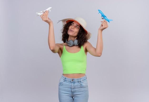 Uma mulher jovem e feliz com cabelo curto em um top verde e chapéu de sol voando em aviões de brinquedo azul e branco sobre um fundo branco