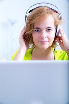 Uma mulher jovem e plus size ouvindo áudio na frente de um laptop.