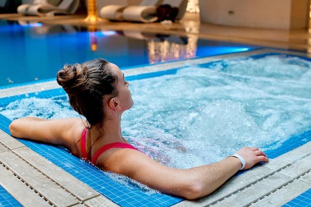 Uma mulher jovem e saudável relaxando sozinha na banheira no resort spa de bem-estar.