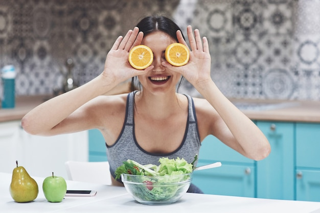 Uma mulher jovem esportes desfruta de uma salada de frutas. ser brincalhão cobrindo os olhos com laranja