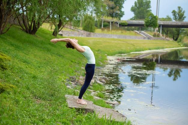 Uma mulher jovem esportes pratica ioga em um gramado verde junto ao rio, postura de yoga assans. meditação e unidade com a natureza