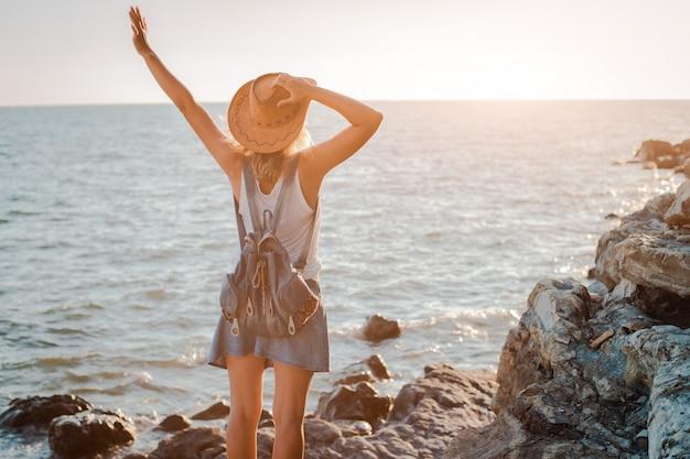 Uma mulher jovem hippie no chapéu e rukzak com as mãos para cima