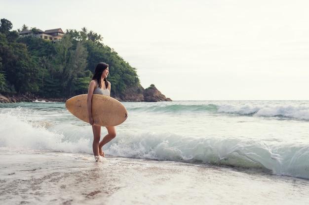 Uma mulher jovem sexy asiática andando na praia com prancha de surf em phuket tailândia