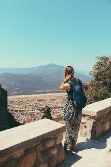 Uma mulher jovem turista com uma mochila fica em um ponto de alta montanha