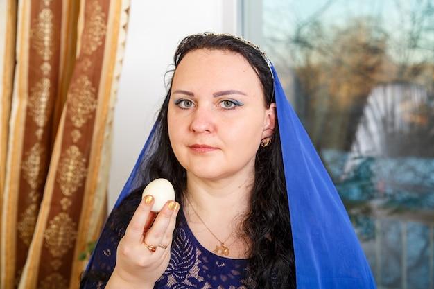 Uma mulher judia com a cabeça coberta por uma capa azul na mesa do seder da páscoa come um ovo. foto horizontal