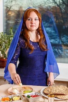 Uma mulher judia com a cabeça coberta por uma capa azul na mesa do seder da páscoa cumpre o mandamento karpas