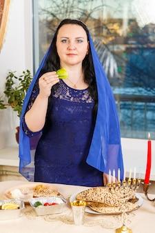 Uma mulher judia com a cabeça coberta por uma capa azul na mesa do seder da páscoa está comendo moror hazeret matzá