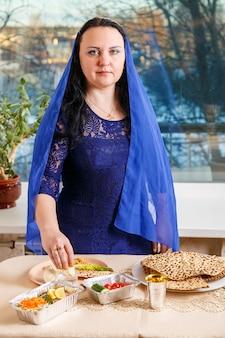 Uma mulher judia com a cabeça coberta por uma capa azul na mesa do seder da páscoa executa o mandamento karpas com uma reverência