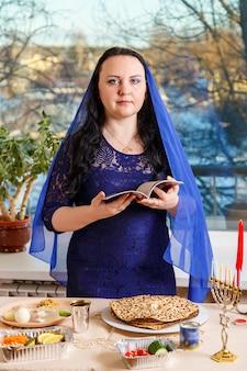 Uma mulher judia com a cabeça coberta por uma capa azul na mesa do seder da páscoa lê a hagadá da páscoa