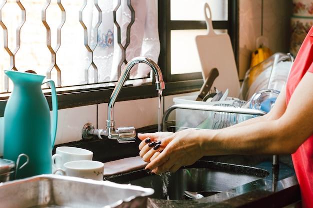 Uma mulher lava as mãos na pia cheia de pratos sujos