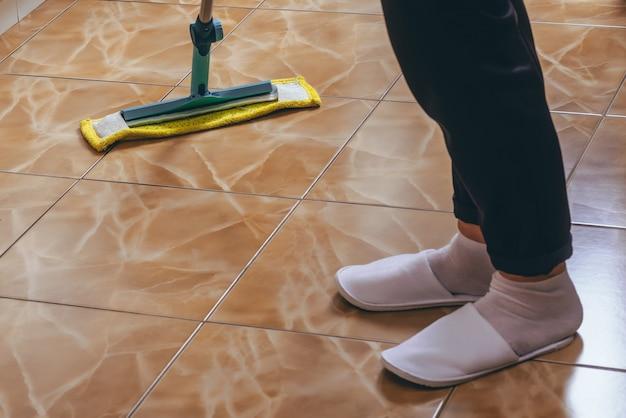 Uma mulher lava o chão de azulejos da cozinha com uma esfregona