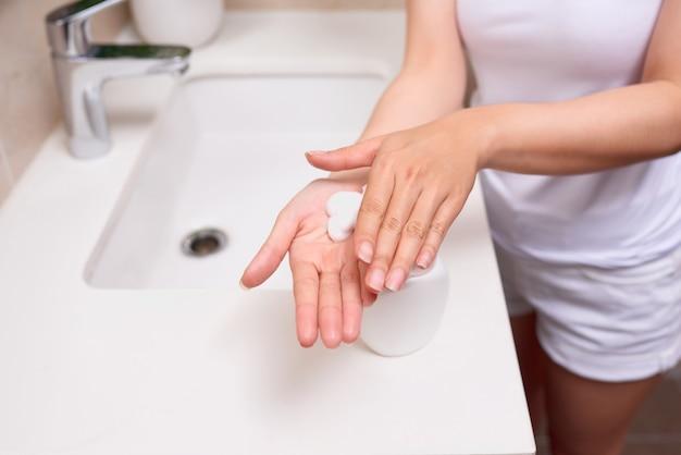 Uma mulher lavando as mãos com uma espuma de sabão.