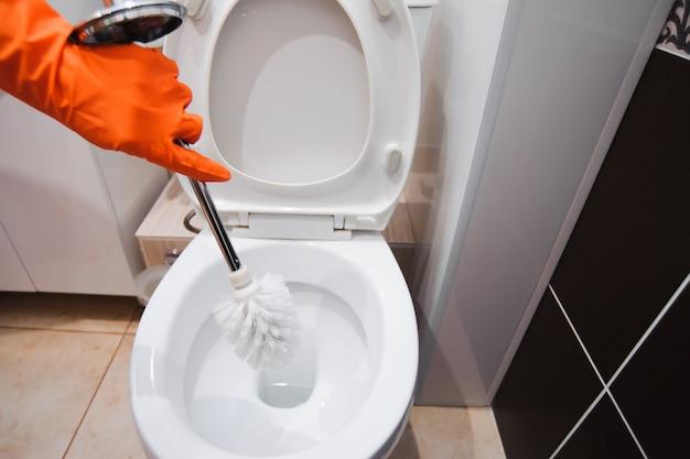 Uma mulher limpa um banheiro com uma escova