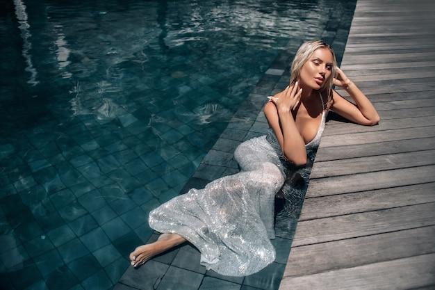 Uma mulher linda de cabelos loiros com os olhos fechados em um vestido longo branco deitado na piscina.
