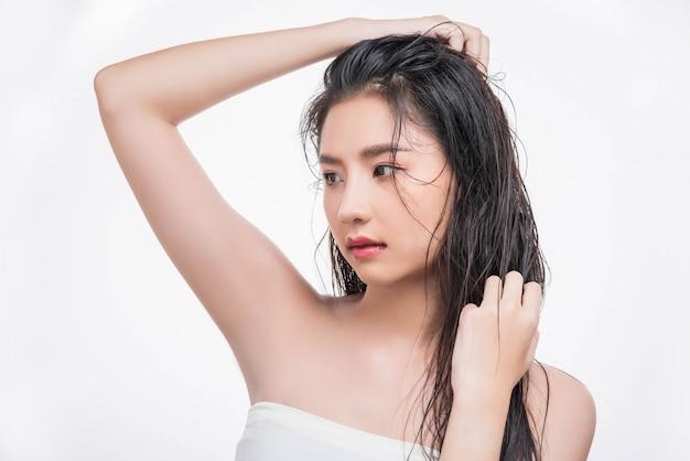 Uma mulher linda e linda pega seu cabelo bagunçado.