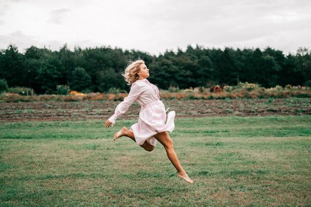 Uma mulher linda em um vestido branco com um ornamento salta no campo