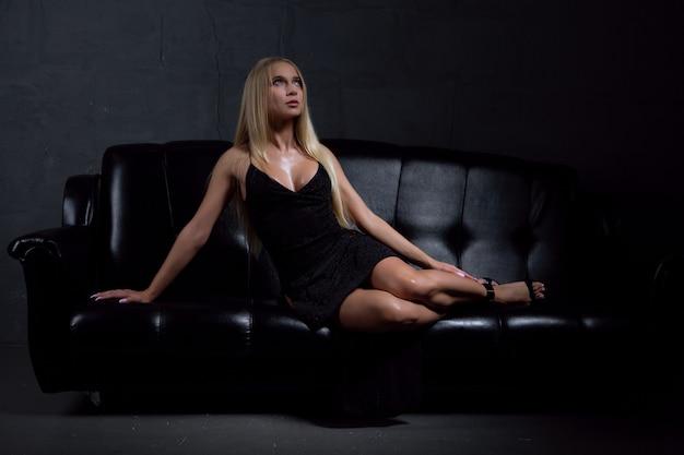 Uma mulher linda em um vestido de noite preto sexy está deitada em um sofá de couro preto.