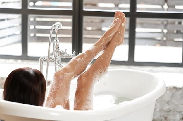 Uma mulher linda está se divertindo em uma banheira branca, em uma sala iluminada com uma grande janela.