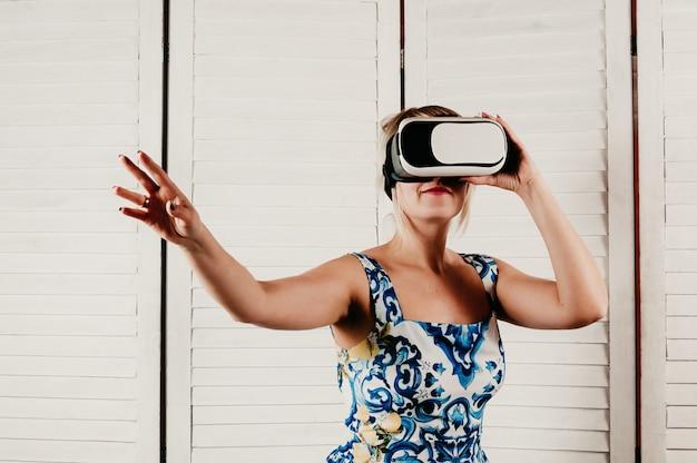 Uma mulher loira atraente usando óculos de realidade virtual, tocando algo com a mão no ar