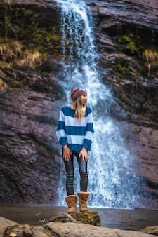 Uma mulher loira cabelos lisos sorridente em uma cachoeira. sessão de estilo de vida