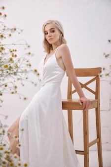 Uma mulher loira com um vestido de noiva branco em pé em casa entre buquês de flores silvestres
