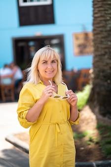 Uma mulher loira com um vestido de verão amarelo está parada na rua da cidade velha de la laguna, na ilha de tenerife. espanha, ilhas canárias
