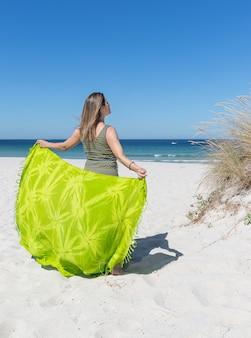 Uma mulher loira de meia-idade nas costas segurando um sarongue verde na praia