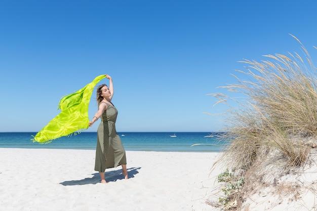 Uma mulher loira de meia idade segurando um sarongue verde ao vento na praia