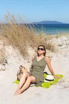 Uma mulher loira de meia-idade, sentada na areia de uma duna na praia