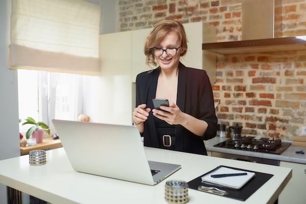 Uma mulher loira de óculos trabalha remotamente em sua cozinha. uma garota feliz com aparelho navega notícias na internet com seu smartphone em casa.