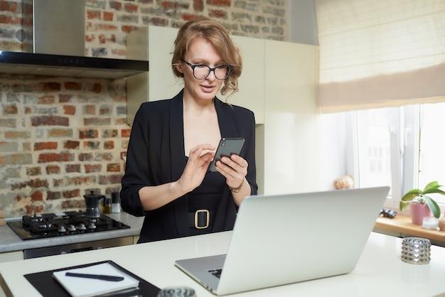 Uma mulher loira de óculos trabalha remotamente em sua cozinha. uma garota séria, navegando com calma notícias na internet com seu smartphone em casa.