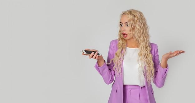 Uma mulher loira envergonhada e excitada não sabe o que fez de errado, encolhe os ombros e encolhe os ombros, chateada, segura um smartphone