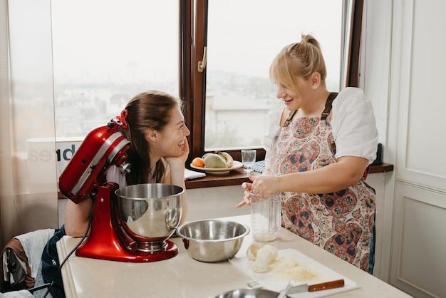Uma mulher loira está amassando suco de limão com a mão no copo do liquidificador perto de sua amiga sorridente na cozinha.