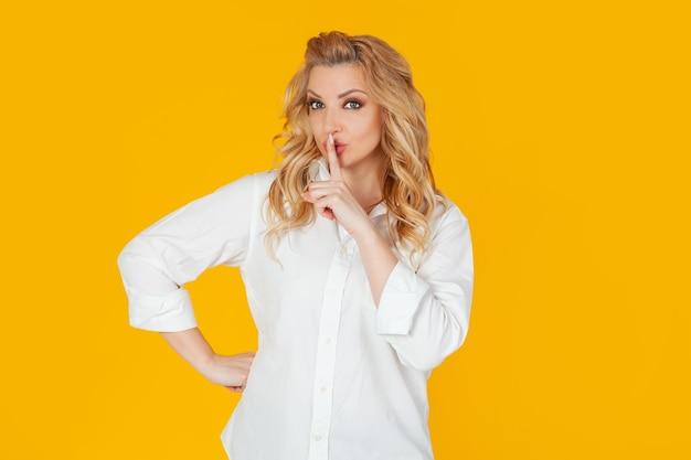 Uma mulher loira europeia séria e dominadora, de camisa branca, diz: cale a boca, fique quieta, protegendo a câmera, pressionando o dedo indicador nos lábios, repreendendo por ter falado muito alto.
