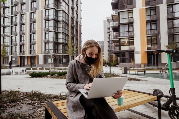 Uma mulher loira veio a este parque em uma scooter elétrica. ela está sentada no banco, usando seu laptop moderno e conversando por videochamada com as amigas. máscara facial médica preta no rosto. hábitos ecológicos.