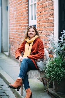 Uma mulher loura bonita nova está sentando-se na cadeira e está apreciando a rua urbana pequena em lubeque.