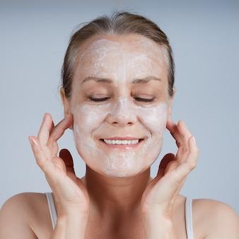 Uma mulher madura aplica uma máscara cosmética no rosto, fechando os olhos. cuidado para o envelhecimento da pele.