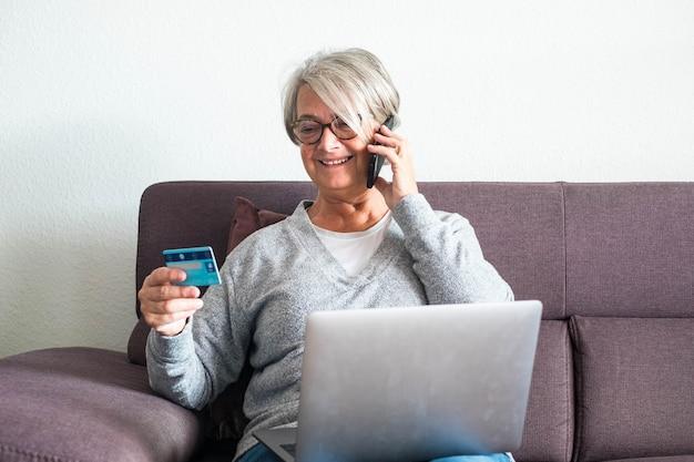Uma mulher madura no sofá usando seu laptop e seu cartão de crédito enquanto chama alguém para comprar algo - conceito de compras online e shopaholic