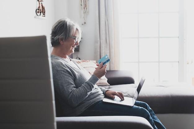 Uma mulher madura ou idosa em casa no sofá usando seu laptop ou pc, gastando dinheiro e comprando online com seu cartão de crédito - compras online entediado em casa na sexta-feira negra ou na cibernética segunda-feira