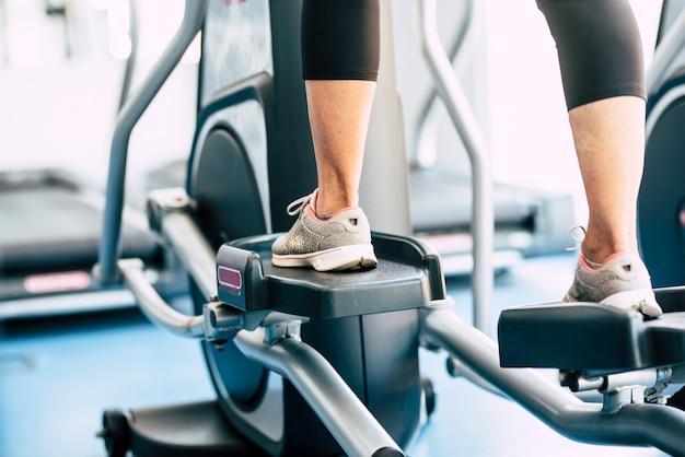 Uma mulher madura ou idosa na academia treinando e fazendo exercícios em uma máquina - conceito e estilo de vida de aposentado ativo - close-up dos pés