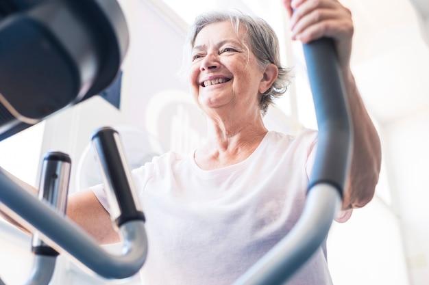 Uma mulher madura ou idosa na academia treinando e fazendo exercícios em uma máquina - conceito e estilo de vida de aposentado ativo