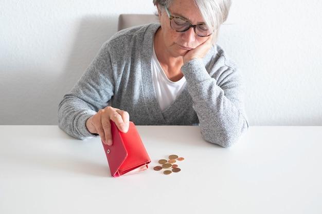 Uma mulher madura recebe o dinheiro que tem menos pela culpa do covid-19 ou crise do coronavírus - idosa perdendo o emprego sem sair de casa por causa da pandemia