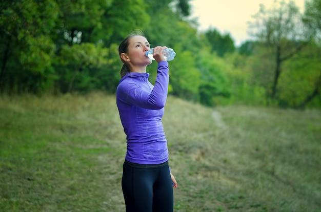 Uma mulher magra caucasiana em uma jaqueta esporte azul com capuz e leggins pretas bebe água da garrafa depois de correr em uma colina de floresta verde colorida.